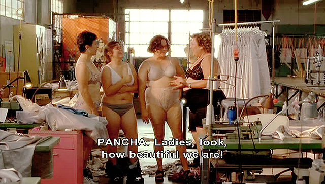 A screencap showing four Latina women standing side by side in their underwear in a clothing factory. There are sewing stations near them. The subtitles read: 'PANCHA: Ladies, look, how beautiful we are!'